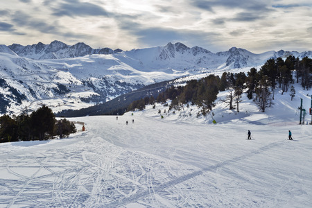 View of flat descent in ski resort. The route with several skiers, the Pyrenees, Andorra, the winter sun through clouds