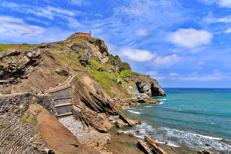 View from the coast on the rock in the ocean with a chapel Doniene Gaztelugatxeko. A chapel Doniene Gaztelugatxeko chapel (San Juan - Gastelugache) in the Basque Country, northern Spain, in the sunny summer day against the blue sky with plumose clouds Stock Photo