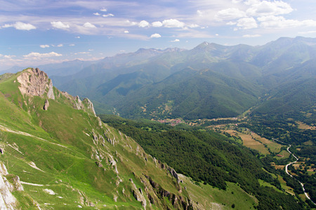 View of mountain and the valley of the village at Fuente de Piedra, Picos de Europa National Park, Cantabria, Spain. The brink of a precipice in the foreground, in the distance tops of mountains. Sunny summer day