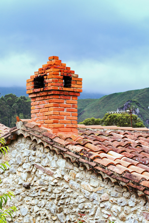 Brick pipe on a roof from a tile. A fragment of the traditional stone house in Spain against the background of the cloudy sky Stock Photo