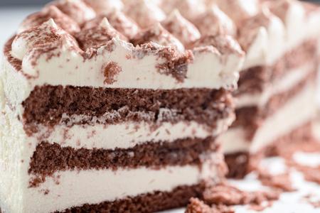 Cut cake close up. Chocolate sponge cake and light cream. Selective focus