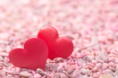 Two hearts on pink stones. Concept of love for Valentines Day