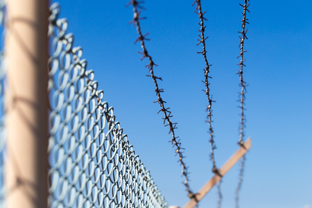 Mesh fence with barbed wire on a background of the blue sky