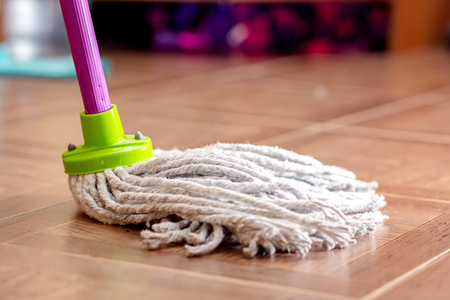 Rope mop for cleaning the floor is on the floor of the tile.