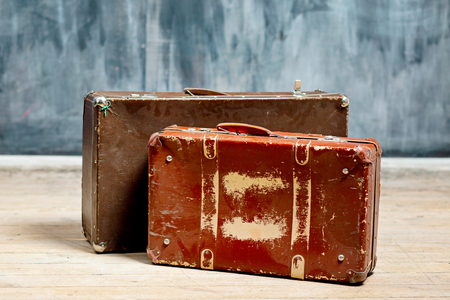 Two brown shabby suitcases near a dark wall in chalk