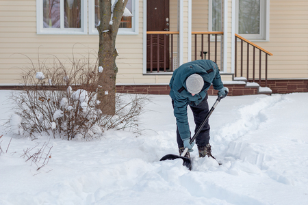 A man removes snow near a country house, clears the path