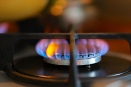 Blue flame of a burning gas stove burner. Close-up, selective soft focus