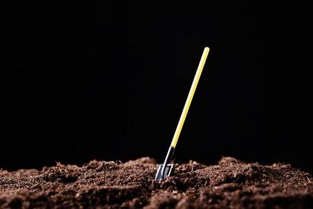 Pelle avec un manche jaune enfoncé dans le sol.