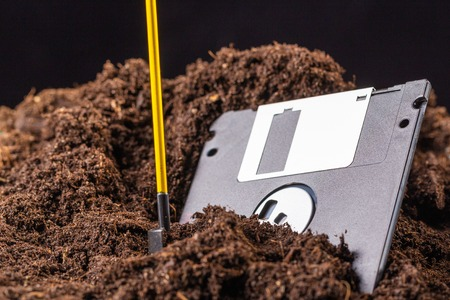 The diskette is half buried in the ground, next to a shovel Stock Photo