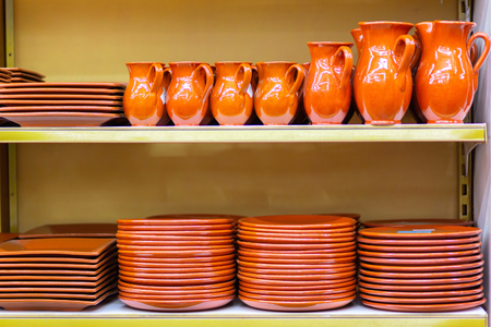Ceramic crockery jugs and plates are on the store shelf.