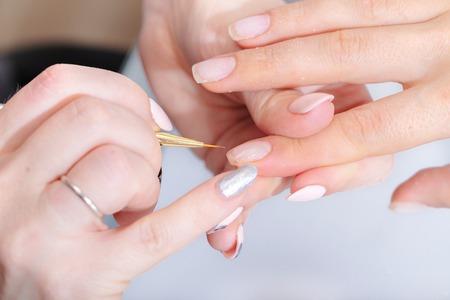 Le mani del maestro dell'hardware manicure e le mani del cliente in primo piano durante l'applicazione di Varn Archivio Fotografico
