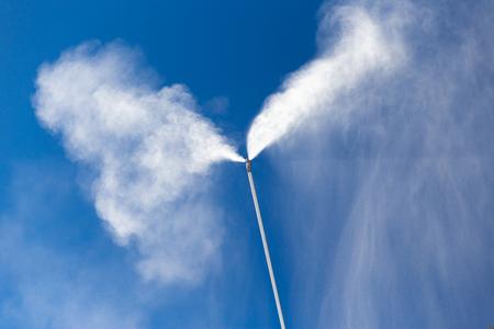 A snow cannon sprays snow against a blue sky Stok Fotoğraf