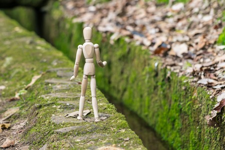 Wooden man on the edge of the canal levada on Madeira with green moss.