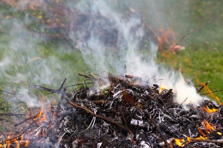 A large pile of burning branches and leaves with smoke. Reklamní fotografie