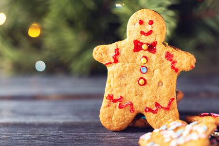 A traditional Christmas cookie in the shape of a man against the background of a Christmas tree with a festive glowing garland.