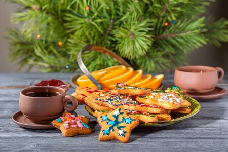 Christmas ginger cookies near the New Year tree on a wooden table.