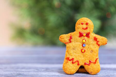 Traditional Christmas cookie in the shape of a man on a background of the Christmas tree