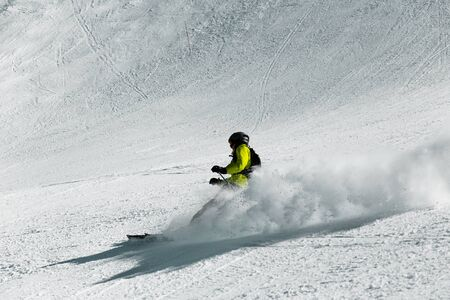 A skier at high speed descends from the mountain.