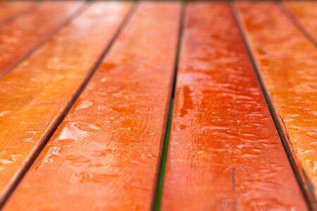 Garden orange wooden table wet after rain.
