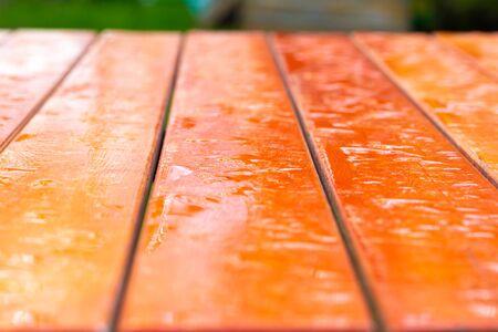 Wet boards in a bright orange garden table