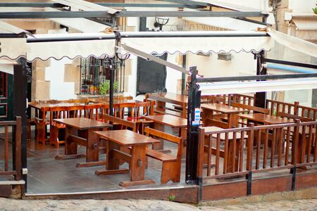 Veranda cafe with wooden furniture without visitors. Cafe in the historical center of the ancient European city