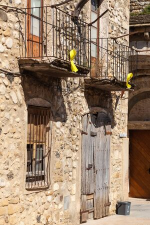 A symbol of the independence of Catalonia on the balconies of an old Spanish building. Yellow ribbons on the background of a very old dilapidated house Foto de archivo