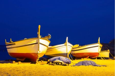 Three fishing boats on a sandy beach in the evening against the background of the sea. Lighting from lanterns, seashore in the Spanish city of Tossa de Mar