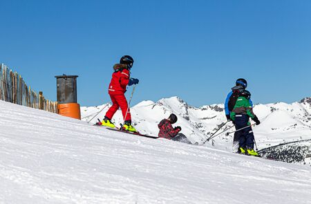 YRENEES, ANDORRA - FEBRUARY 15, 2019: Skiers at the beginning of the descent begin to move on a frosty winter day.