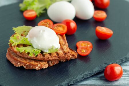 Poached egg on toasted bread cereal on a slate board.