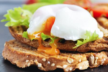 The yolk from a poached egg flows onto the bread.