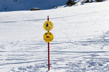Signs in the mountains at a ski resort with hazard warnings.