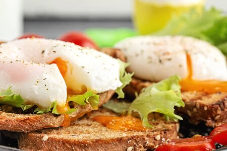 Breakfast toasts and poached eggs, served with lettuce and tomatoes.