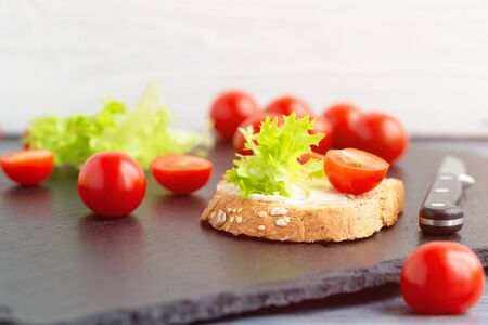 Sandwiches with soft cheese, lettuce and tomatoes on grain bread. Close-up, blurry background, selective focus