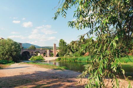 View of the stone bridge over the Fluvia River in Besalu, Catalonia on a summer day.