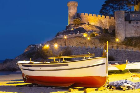 Fishing boat on a sandy beach in the evening against the background of the fortress.
