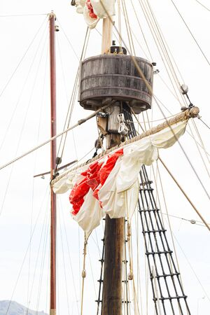 Tackles of an old sailing vessel - a mast, a mast, raised red-white sails, ropes. Fragment of a restored copy of the ship against a cloudy sky