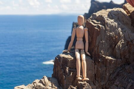 The wooden man crouched down to rest on the rocks against the ocean. The concept of outdoor activities and tourism Stock Photo
