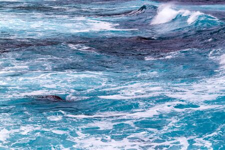 Natural background from foaming ocean waves, view from above. The color of the waves varies from dark blue to bright turquoise Banco de Imagens