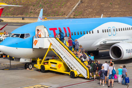 Funchal, Madeira - August 4, 2018: Tourists land on a plane at the airfields in Madeira. Gangway going towards the aircraft. Sunny summer day, good weath Editorial