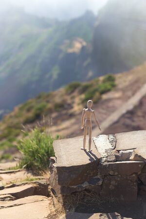A wooden man stands on a cliff of a mountain at the precipice and looks into the distance in the sun. The concept of optimism and hope for a brighter future