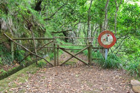A sign climbs a passage along a dangerous path along a levada in Madeira, Portugal. Access to routes dangerous to tourists is prohibited