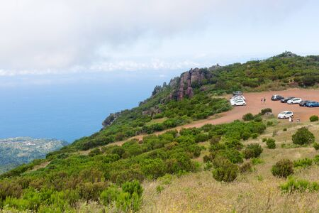 A view of the parking lot from the trail to Pico de Ruivo in Madeira, Portugal. The slope of the mountain, overgrown with shrubs, the ocean in the distance on the horizon Banco de Imagens