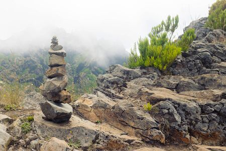 Pyramid of stones on a hiking trail in the mountains of Madeira. Banco de Imagens
