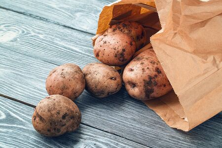 The tubers of potatoes fell out of a paper bag on a wooden table