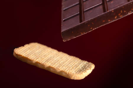 A bar of chocolate and cookies on a brown background with a gradient. Biscuits and chocolate hang in the air without support
