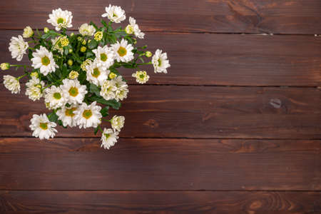 A bouquet of white bush chrysanthemums on a wooden table in the upper left corner. View from above, brown table, free seat on the right