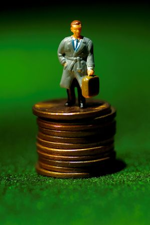 Miniature Businessman Standing on a Stack of Pennies