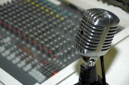soundboard: Vintage Microphone and Mixing Board in Background