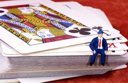 Deck of cards with a miniature man sitting on them.