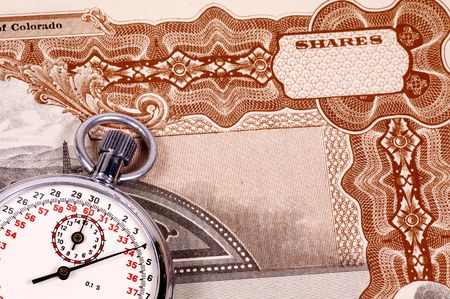 timing: Stopwatch and a Stock Certificate - Market Timing Concept